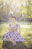 Jonge vrouw met lange haarzitting in de lezing van de vensterzetel royalty-vrije stock afbeelding