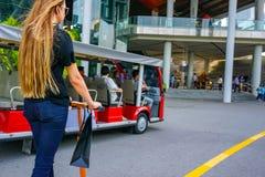 Jonge vrouw met lange haren op elektrische autoped Het meisje op de elektrische autoped drinkt koffie royalty-vrije stock foto
