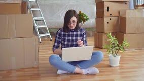 Jonge vrouw met laptop onder dozen voor zich het bewegen stock videobeelden