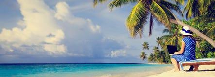Jonge vrouw met laptop op tropisch strand royalty-vrije stock afbeelding