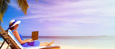 Jonge vrouw met laptop op tropisch strand Stock Fotografie