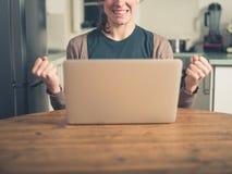 Jonge vrouw met laptop vuist het pompen in keuken Stock Foto