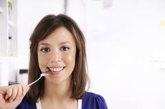 Jonge vrouw met lepel op lippen Stock Fotografie