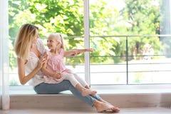 Jonge vrouw met leuk meisje dichtbij venster thuis Royalty-vrije Stock Afbeeldingen