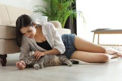 Jonge vrouw met leuke kat thuis stock foto