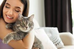 Jonge vrouw met leuke kat thuis huisdier en eigenaar stock fotografie