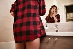 Jonge vrouw met lippenstift in badkamers royalty-vrije stock foto's