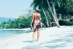 Jonge vrouw met longboard het in hand lopen op wit zand royalty-vrije stock foto