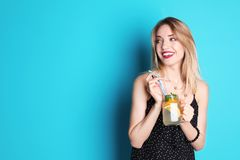 Jonge vrouw met metselaarkruik smakelijke limonade op kleurenachtergrond Natuurlijke detoxdrank Royalty-vrije Stock Afbeeldingen