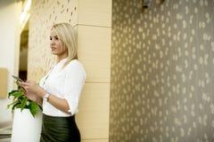 Jonge vrouw met mobiele telefoon in het bureau Stock Fotografie
