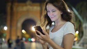 Jonge vrouw met mobiele telefoon tegen Arc DE Triomf in Barcelona stock videobeelden