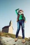 Jonge vrouw met modieuze hoed en een oude romanesque kerk Archan Stock Fotografie