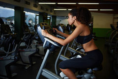 jonge vrouw met mooi cijfer die een hometrainer met behulp van bij de gymnastiek Stock Fotografie