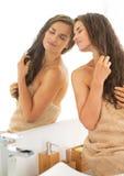 Jonge vrouw met natte haarzitting in badkamers Stock Fotografie