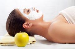 Jonge vrouw met natuurlijke gezichtsmasker en appel royalty-vrije stock afbeeldingen