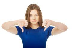Jonge vrouw met neer duimen Stock Afbeelding