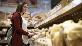 Jonge vrouw met oogglazen die vers brood in de supermarkt ruiken stock footage