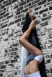 Jonge vrouw met opgeheven benen, leunend op een muur Stock Foto