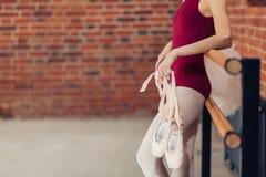 Jonge vrouw met pointeschoenen in handen die op de balletstaaf leunen stock foto