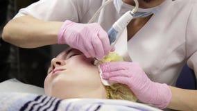 Jonge vrouw met probleemhuid, het mechanische diepe gezicht schoonmaken de schoonheidsspecialist reinigt de huid van de vrouw met stock video
