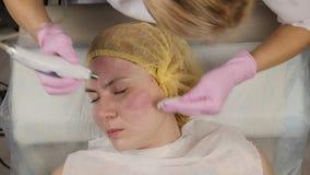 Jonge vrouw met probleemhuid, het mechanische diepe gezicht schoonmaken de schoonheidsspecialist reinigt de huid van de vrouw met stock videobeelden