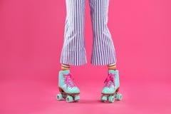 Jonge vrouw met retro rolschaatsen op kleurenachtergrond stock afbeelding