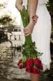 Jonge vrouw met rode rozen dichtbij de rivier Stock Afbeeldingen