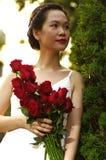Jonge vrouw met rode rozen in het park Royalty-vrije Stock Afbeelding