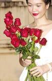 Jonge vrouw met rode rozen in het park Stock Foto's