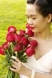 Jonge vrouw met rode rozen in het park Stock Foto