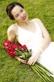 Jonge vrouw met rode rozen in het park Royalty-vrije Stock Afbeeldingen