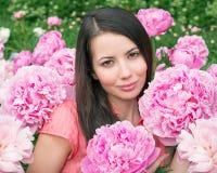 Jonge vrouw met roze pioenen stock afbeeldingen