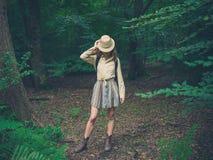 Jonge vrouw met safarihoed in bos Stock Afbeeldingen