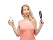 Jonge vrouw met schaar en haarborstel royalty-vrije stock foto's