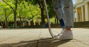 Jonge vrouw met skateboard die zich in de stad 4k bevinden stock video