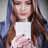 Jonge vrouw met slimme telefoon het luisteren muziek Royalty-vrije Stock Foto