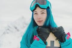 Jonge vrouw met snowboard in de winter stock fotografie