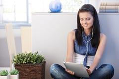 Jonge vrouw met tablet die thuis glimlachen stock afbeeldingen