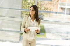 Jonge vrouw met tablet in het bureau Stock Foto's