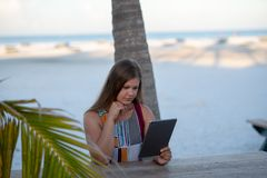 Jonge vrouw met tablet op het strand stock afbeelding