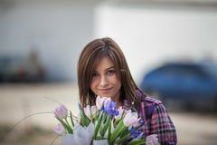 Jonge vrouw met tulpen in handen Stock Afbeelding