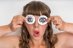 Jonge vrouw met twee katoenen stootkussens aan haar ogen stock fotografie