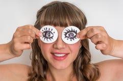 Jonge vrouw met twee katoenen stootkussens aan haar ogen stock foto's