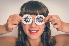Jonge vrouw met twee katoenen stootkussens aan haar ogen royalty-vrije stock foto's