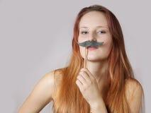 Jonge vrouw met valse snor stock afbeelding