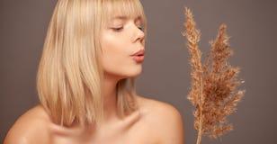 Jonge vrouw met verse gezonde huid en haren die droge bloemen en het glimlachen houden De kosmetiek, schoonheid en kuuroord stock foto's