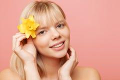 Jonge vrouw met verse gezonde huid en haren die narcissen en het glimlachen houden De kosmetiek, schoonheid en kuuroord Roze stock afbeeldingen