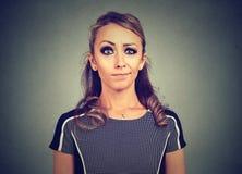 Jonge vrouw met verwarde twijfelachtige en niet afdoende gezichtsuitdrukking stock foto's