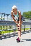 Jonge vrouw met verwond knie of been in openlucht stock fotografie