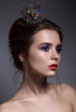 Jonge vrouw met violette samenstelling en kroon Royalty-vrije Stock Afbeeldingen